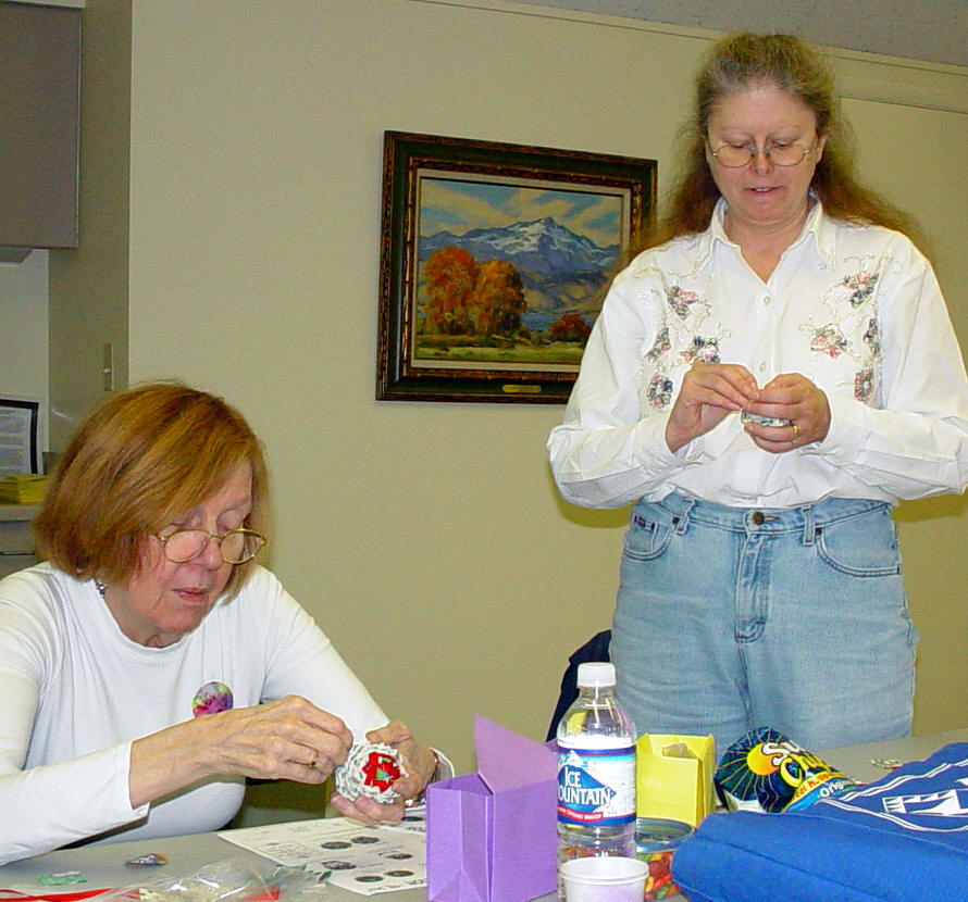 Mike Loibl works on a Christmas Ornament with Donna Fousek